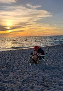 A teenage boy and his border collies on the beach in Florida.
