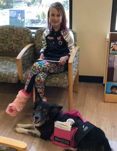 A young girl sits in a hospital waiting room with her border collie service dog.