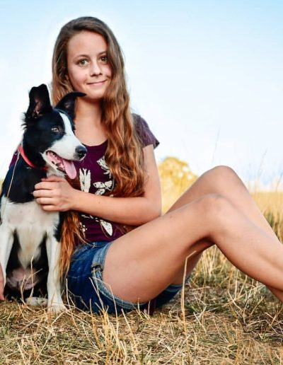 A beautiful teenage girl posing in a field with her black and white border collie puppy.