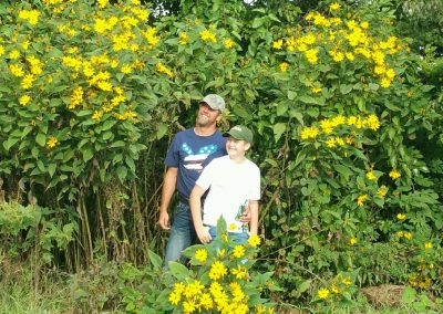A father and son hugging beside beautiful yellow flowers.