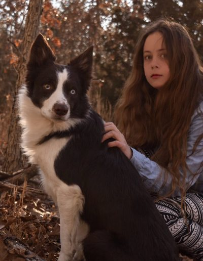 A young girl in the forest, on a hike, with her red and white border collie.
